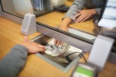 Bediende die contant geldgeld geven aan klant op bankkantoor stock afbeelding