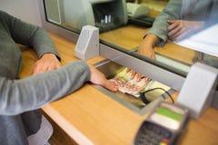 Bediende die contant geldgeld geven aan klant op bankkantoor stock afbeeldingen