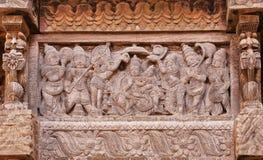 Bedienden en bewonderaars van de Indische god op gesneden houten muur van traditionele Hindoese tempel Stock Foto's