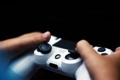 Bedieningshendel in spel in zwarte wordt geïsoleerd die Close-up die van handen gamepad op zwarte achtergrond houden stock foto's