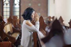 Bedjande förlåtelse för ung kvinna i kyrka royaltyfri foto