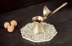 Bednarzy tureckiego Cezve z czarną kawą na wzorzystej ceramicznej tacy i orzechach włoskich obraz stock