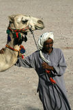 Bedouin. With his camel in desert Stock Photography