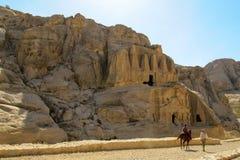 Bedouin begeleidt een toeristenruiter op een paard op de achtergrond van oude rotsen en holt uit royalty-vrije stock foto's