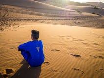 Bedouin boy wearing a blue djellaba and orange scarf standing
