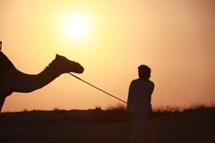 Bedouin with camel. A bedouin pulling a camel through the desert royalty free stock photos