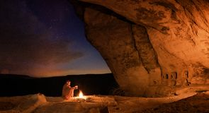 Bedouin in the Crimean cave Kachi-Kalyon is heated by the fire on the background of the starry sky stock photography
