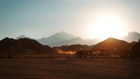 Bedouin dorp in woestijn in bergen in zonsondergang Stock Foto
