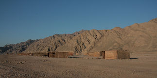 Bedouin huts in the desert. Mountain range with bedouin huts on the beach in front of it Stock Image