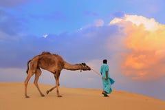 Bedouin leading his camel in Thar desert near Jaisalmer, India Stock Photos