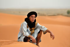 Bedouin man wears traditional clothing in Sahara desert. Unidentified bedouin man wears traditional clothing in Sahara desert in Morocco, August 03, 2015. The Stock Photo