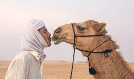 Bedouin mens die zijn kameel kussen stock foto