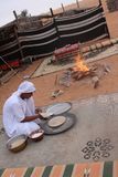 A Bedouin Prepares Bread by the Fire in Wahiba Sands in Oman stock images