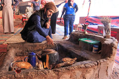 Bedouin serving tea to the tourists visiting the bedouin camp in the Wadi Rum desert, Jordan stock image