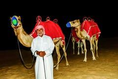 Bedouin standing in front of his Camel in the arabian desert Stock Photos