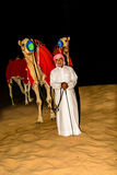 Bedouin standing in front of his Camel in the arabian desert Stock Images