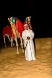 Bedouin standing in front of his Camel in the arabian desert Stock Images