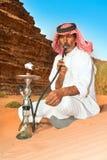 Bedouin in Wadi Rum, Jordan. Bedouin with nargiila in the desert, Wadi Rum, Jordan stock photo