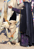 Bedouin woman in black clothes with a raised hand next to a camel. Royalty Free Stock Photos