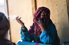 Bedouin woman smokes a cigarette. In an oasis Stock Photo