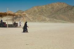 Bedouin woman walking in the desert Royalty Free Stock Photo