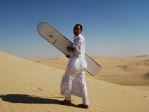 Bedouine man sand-boarding on dunes Royalty Free Stock Photo