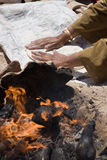Bedouins bread. Bedouin woman is kneading dough for bread with burning fire in the foreground Stock Photography