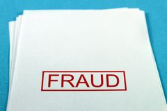 Bedrägeriord på ett papper på ett blått skrivbord arkivfoto