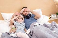 Bedrövlig förkylda flicka och pappa Royaltyfri Foto