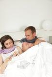 Bedrövliga sjuka barnpar i säng Arkivbilder
