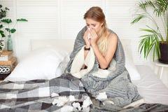Bedrövligt sammanträde för ung kvinna på sängen som slås in i den varma filten som känner sig sjuk med influensa royaltyfria bilder