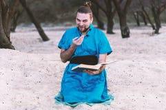 Bedra omkring den stiliga skäggiga mannen som sitter i blå kimono och att rymma boken och att se kameran royaltyfria bilder