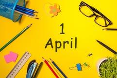 Bedrar dagen - April 1st dag 1 av den april månaden, kalender på gul skolaskrivbordbakgrund Fjädra den tid… ron lämnar, naturlig  Royaltyfri Foto