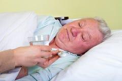Bedridden elderly man having high temperature Royalty Free Stock Photography