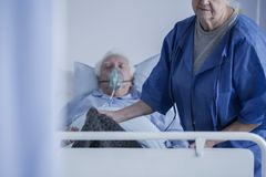 Bedridden man wearing oxygen mask. Bedridden men wearing an oxygen mask lying in a hospital with his wife covering his feet with a blanket stock photos