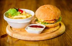 Bedrieg maaltijd Heerlijke hamburger met sesamzaden Hamburgermenu Hoge caloriesnack Hamburger en frieten en tomaat royalty-vrije stock afbeeldingen