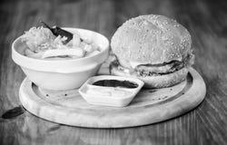 Bedrieg maaltijd Heerlijke hamburger met sesamzaden Hamburgermenu Hoge caloriesnack Hamburger en frieten en tomaat stock afbeelding