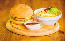 Bedrieg maaltijd Heerlijke hamburger met sesamzaden Hamburgermenu Hoge caloriesnack Hamburger en frieten en tomaat stock foto
