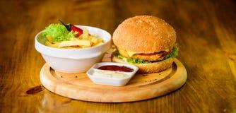 Bedrieg maaltijd Heerlijke hamburger met sesamzaden Hamburger met kaasvlees en salade Snel voedselconcept Hamburgermenu hoog stock afbeeldingen