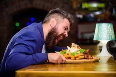 Bedrieg maaltijdconcept Hongerige Hipster eet bar gebraden voedsel Zit het manager formele kostuum bij barteller Heerlijke Maalti stock foto