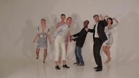 Bedrijf van dansende jonge mooie vrouwen en aantrekkelijke mannen tussen verschillende rassen in studio stock videobeelden