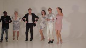 Bedrijf van dansende jonge mooie vrouwen en artistieke mannen tussen verschillende rassen in studio stock video
