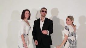 Bedrijf van dansende jonge mooie vrouwen en de aantrekkelijke mens in kostuum en zonnebril stock videobeelden