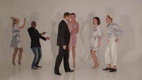 Bedrijf van dansende jonge mooie wijfjes en knappe mannetjes tussen verschillende rassen in studio stock videobeelden