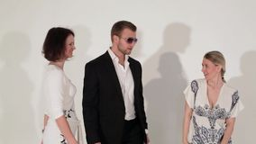 Bedrijf van dansende leuke meisjes en mooie kerel in kostuum en zonnebril stock videobeelden