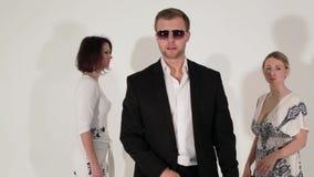 Bedrijf van dansende leuke vrouwen en de mooie mens in kostuum en zonnebril stock video
