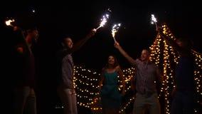 Bedrijf van gelukkige vrienden die bij nacht met heldere toortsen in handen dansen stock footage