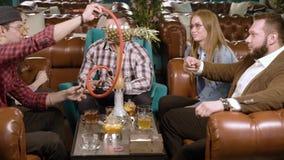 Bedrijf van vrienden die en waterpijp in de koffie babbelen roken stock video