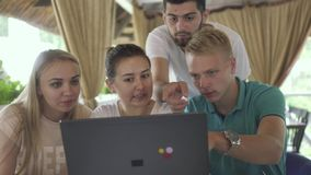 Bedrijf van vrienden die het scherm van laptop in koffie bekijken stock video