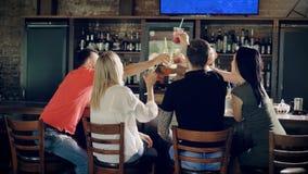Bedrijf van vrienden die verjaardagspartij vieren bij de restaurant clinking glazen met cocktails Mensen die bij zitten stock footage